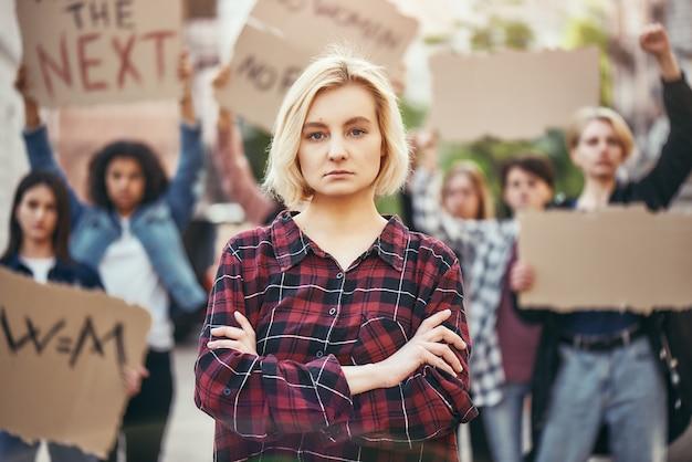 내 권리를 위해 싸우는 젊은 금발 여성이 항의하는 동안 팔짱을 끼고 서 있다