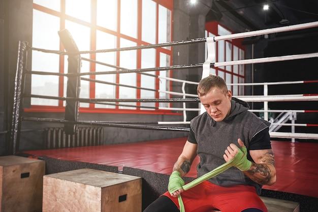 화이팅 준비. 자신감 있는 운동 문신을 한 남자가 녹색 붕대로 손을 감쌌습니다. 싸울 준비가 된 강한 손과 주먹