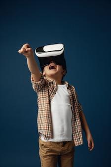 偽の世界との戦い。青いスタジオの背景に分離されたバーチャルリアリティヘッドセットメガネとジーンズとシャツの小さな男の子または子供。最先端技術、ビデオゲーム、イノベーションのコンセプト。