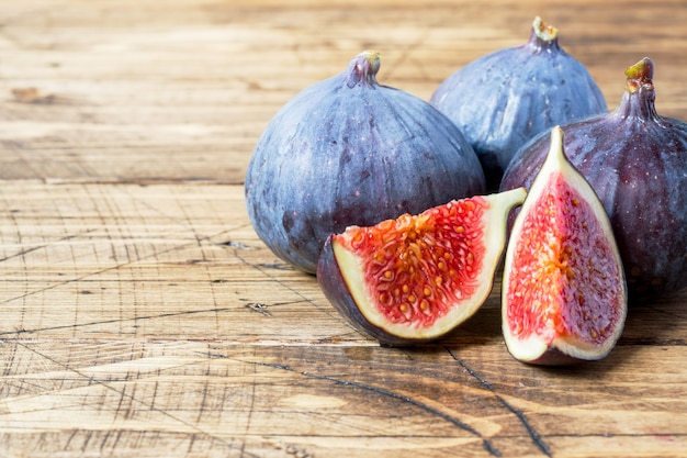 Figs are fresh ripe whole and cut into a wooden old surface.