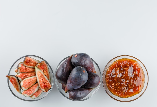 Figs in bowls with fig jam flat lay on a white