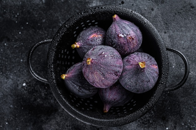 Figs in a colander, organic fruit. black background. top view.