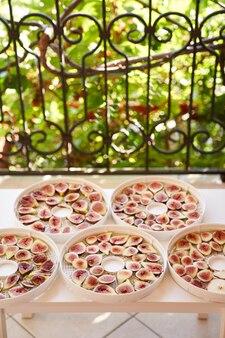 Процесс сушки инжира на тарелках на столе на балконе