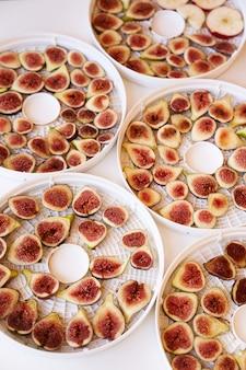 Процесс сушки инжира на тарелках на столе