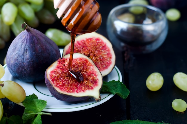 Figs and honey on wooden table background.