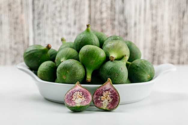 Figs in a plate with slices flat lay on white and grungy wooden wall