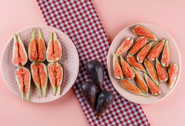 Figs in plates on pink and kitchen towel, flat lay.