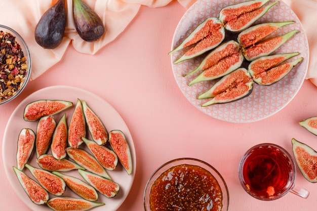 Figs in plates with cup of tea, jam, dried herbs flat lay on pink and textile