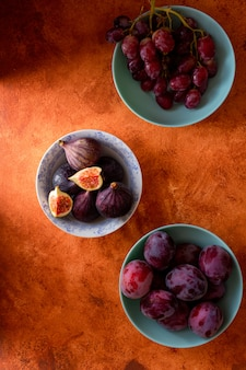 Figs, plums and grape in bowls on orange background. top view