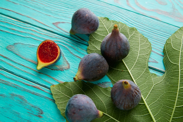 Figs raw cutted fruits and fig tree leaves on blue