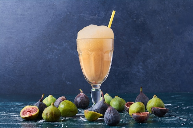 Figs with a cup of drink on blue.