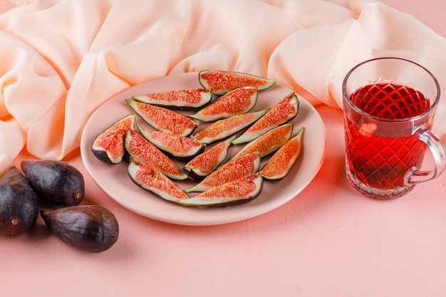Figs with cup of tea in a plate on pink and textile, high angle view.