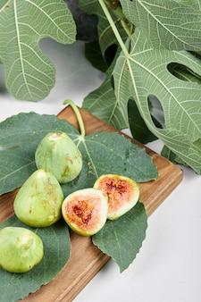 나무 접시에 녹색 잎 무화과.