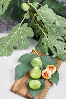 Инжир с зелеными листьями на деревянном блюде.