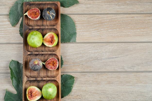 Figs with green leaves on a wooden platter.