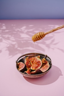 Инжир с медом в железной тарелке на розово-синем фоне