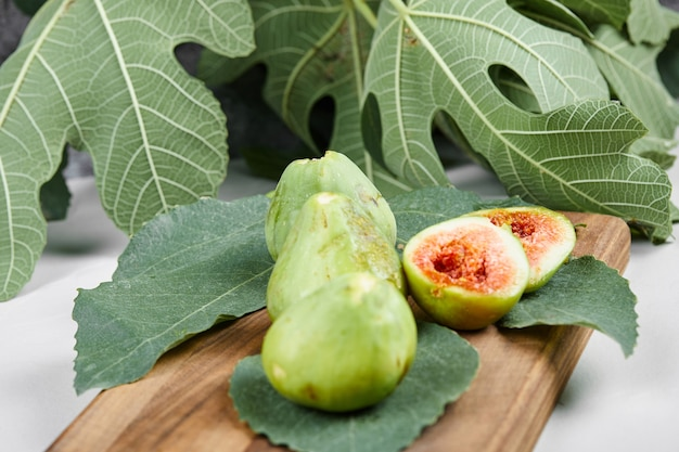 Figs with red seeds on a wooden platter.