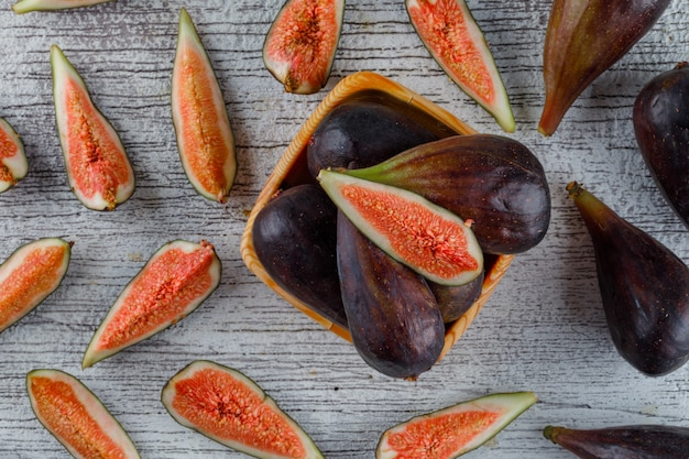 Figs with slices in a wooden plate on grungy, flat lay.
