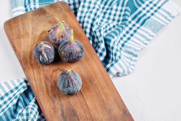 Fichi su tavola di legno con tovaglia blu.