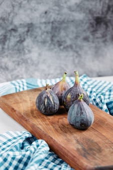 Figs on wooden board with a blue tablecloth.