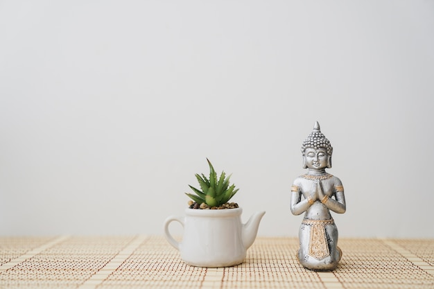 Figure of buddha next to a pot