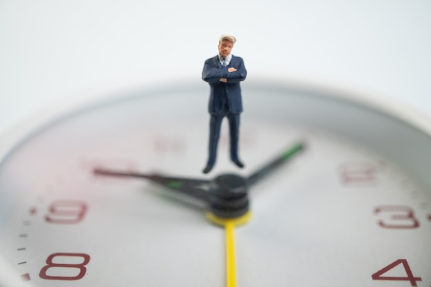 Figure businessmen are thinking and standing on the white watch face by the watch face showing the time.