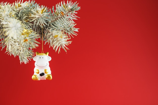 Figure of a cow on a spruce branch, on a red background