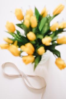 Восьмерка из бежевой ленты с красивыми желтыми тюльпанами в вазе. международный женский день, концепция 8 марта