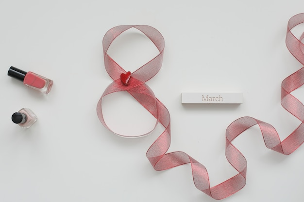 Figure eight of red ribbon and word march on white background.
