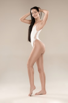 The figure of girl in a swimsuit on studio background