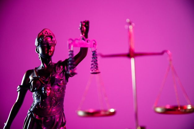 Figure of lady justice in purple neon.