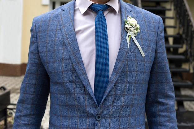 The figure of a man in a blue jacket with a blue tie and a white boutonniere, no face
