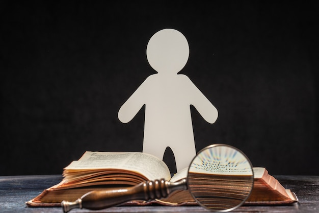 A figure of a man carved from paper standing at an open book. the concept of learning and knowledge.