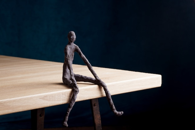 The figure of a man sits on the edge of the table