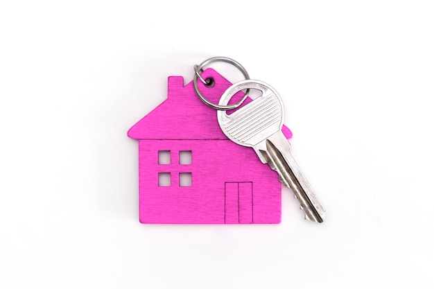 Figure of a mini house of pink color with keys on an isolated white background.