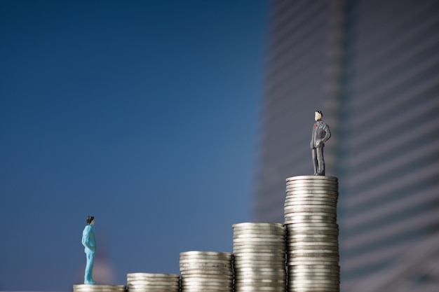 Figure miniature businessman standing on coin stack