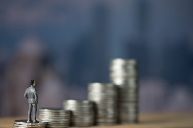 Figure miniature businessman standing on first step of coin stack and look at the top of coin