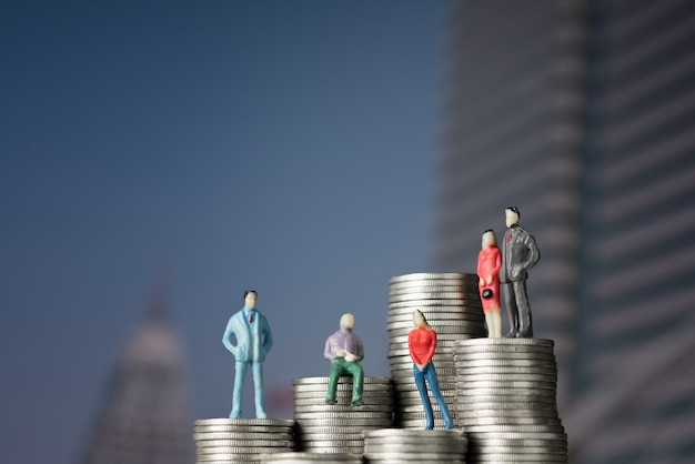 Figure miniature businessman standing on stack of coin
