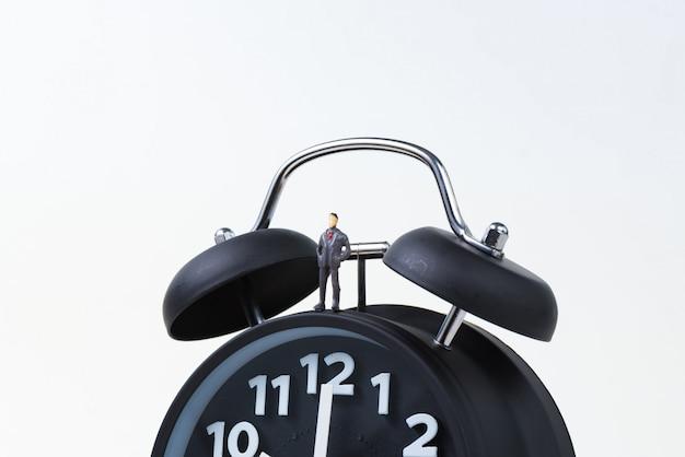 Figure miniature businessman standing with alarm clock