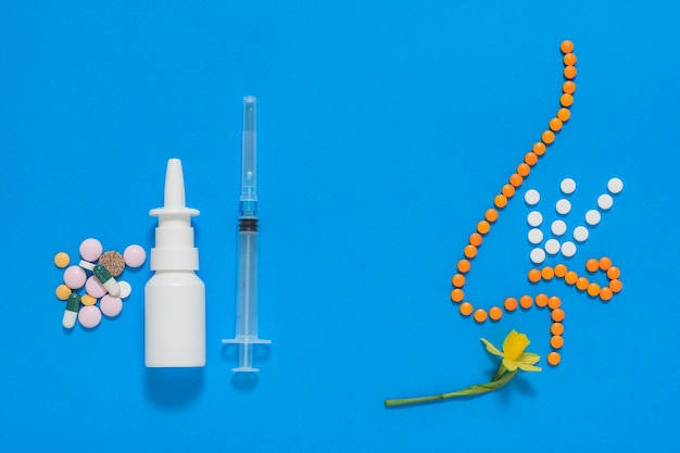 The figure of the nose of the tablets inhaling the fragrance of the flower and allergy remedies on a blue background. the concept of treatment of diseases of the nose and allergies. flat lay.