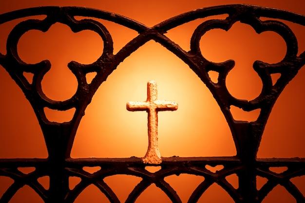 オレンジ色の背景上の十字架の図。クリスチャンクロスシルエット。