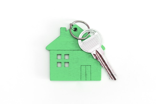 Фигура мини-домика зеленого цвета с ключами на изолированном белом фоне.