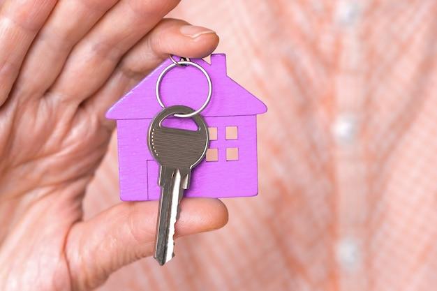 열쇠가 있는 보라색 미니 하우스 그림은 베이지색 배경에 있는 남자의 손에 있습니다