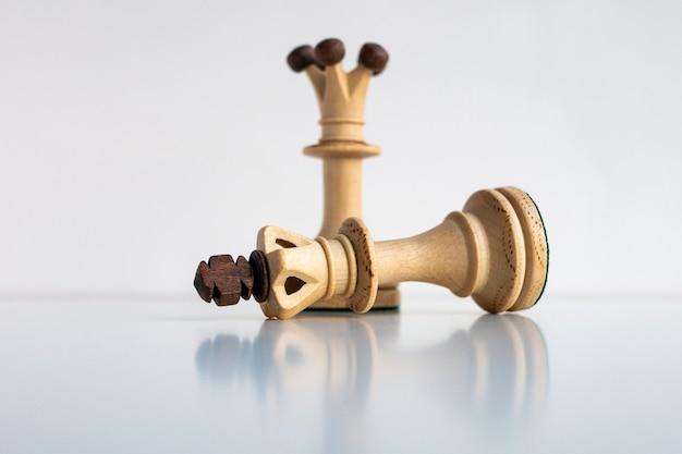 Фигура поверженного шахматного короля на фоне стоящего ферзя.