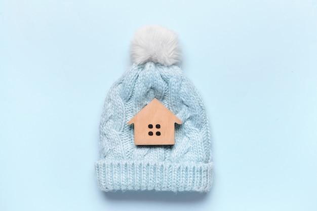 Фигура дома и теплая шляпа на цветном фоне. понятие отопительного сезона
