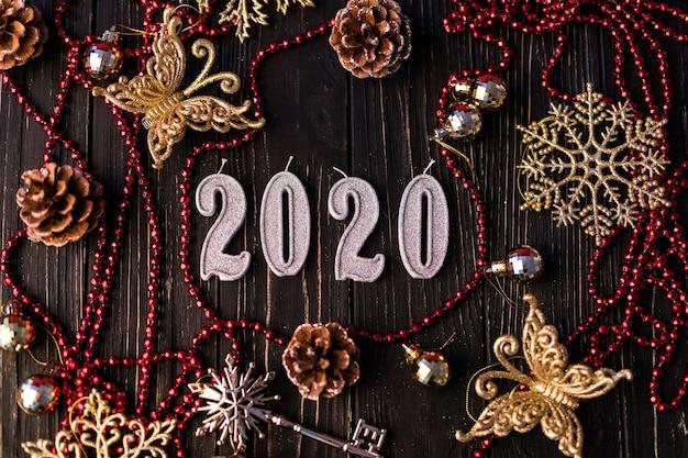 赤いネックレスからの新年の姿。木の板のトウヒの枝、上面図。木製の背景にクリスマスの装飾。コピースペース