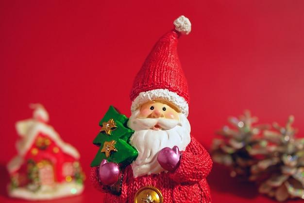 Фигура санта-клауса с елкой в руке на фоне декоративного рождественского домика и леса.