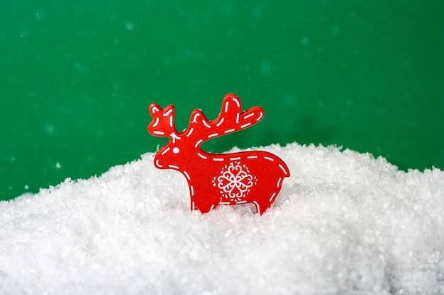 雪片と緑の背景に雪の中で木製のクリスマス鹿の図。
