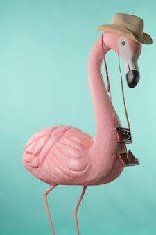 Figure of a pink flamingo tourist in a straw hat holding a camera