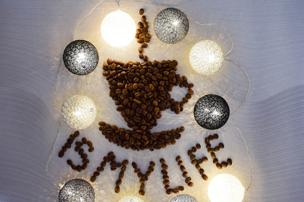A figure in the shape of a cup of coffee with a saucer is made of coffee beans